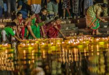 Women sending diyas to float on the river