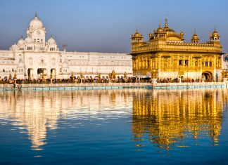 A view of golden temple with its beautiful image in water parallel to it.